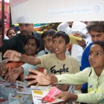 Children in Delhi reach for educational materials